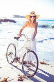 Blonde in sundress with her bike at beach — Zdjęcie stockowe