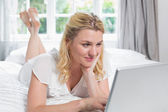 Blonde lying on bed using laptop — Stock Photo