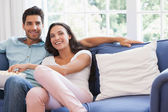 Attractive couple watching tv on the couch — Stock Photo