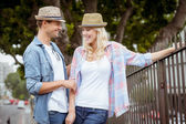 Hip couple standing by railings — Stock Photo