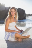 Blonde in sundress using tablet on the beach — Stok fotoğraf