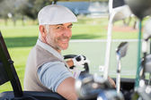 Happy golfer driving his golf buggy — Stock Photo