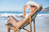 Woman relaxing in deck chair on beach — Stock Photo