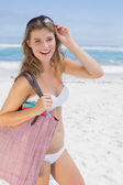Blonde on beach holding bag — Stockfoto