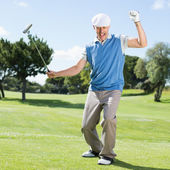 Excited golfer cheering on putting green — Stock Photo