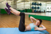 Brunette doing sit ups in fitness studio — Stok fotoğraf