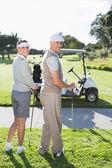 Happy golfing couple turning — Stock Photo