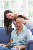 Brunette covering her boyfriends eyes — Stock Photo