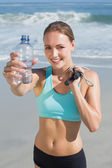 Woman holding water bottle and skipping rope — Stock Photo