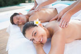 Couple enjoying couples massage poolside — Stock Photo