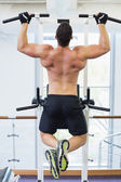 Shirtless bodybuilder doing pull ups — Stock Photo