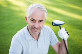 Handsome golfer smiling up at camera — Stock Photo
