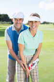 Golfing couple putting ball together — Foto de Stock
