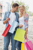 Coppia hip guardando loro shopping bag — Foto Stock