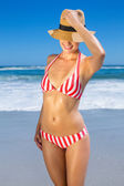 Woman in bikini and sunhat posing on beach — Stock Photo