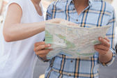 Tourist couple looking at map — Stock Photo
