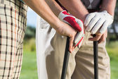 Golfing couple standing holding their clubs — Stock Photo