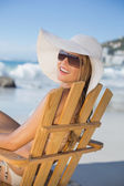 Woman in hat relaxing in deck chair — Stock Photo