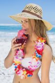 Blonde in floral garland sipping cocktail — Stock Photo