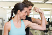 Fit attractive couple comparing biceps — ストック写真