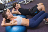 Man and woman doing sit ups on exercise ball — Stock Photo