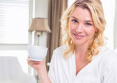 Blonde in bathrobe drinking coffee — Stock Photo