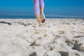 Sportowcy womans nogi jogging na piasku — Zdjęcie stockowe