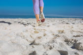 Sporty womans feet jogging on sand — Stock Photo