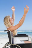 Wheelchair bound blonde on beach — Stock Photo