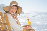 Blonde by the sea holding cocktail — Stock Photo