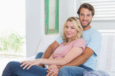 Couple relaxing on couch — Stockfoto