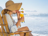 Blonde sipping cocktail by the sea — Stock Photo
