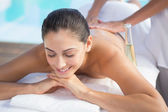 Brunette enjoying a massage poolside — Stock Photo