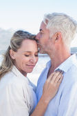 Man kissing his partner at the beach — Stock Photo