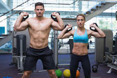 Bodybuilding man and woman lifting kettlebells — Stock Photo
