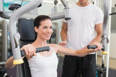 Brunette using weights machine with trainer — Stock Photo