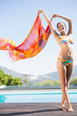 Beautiful brunette in bikini holding sarong up — Stock Photo