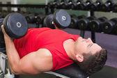 Bodybuilder liggend op de bank opheffing van halters — Stockfoto