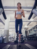 Fit woman running on the treadmill — Stock Photo