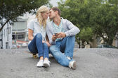 Hip couple sitting on skateboard kissing — Stock Photo