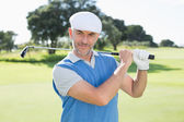 Golfer standing and swinging his club — Stock Photo