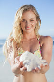 Blonde in bikini holding conch — Stock Photo