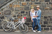 Hip couple hugging by wall with bikes — Stock fotografie