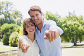 Couple pointing to the camera in the park — Stock Photo