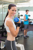 Fit brunette lifting blue dumbbell — Stock Photo