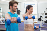 Couple exercising with dumbbells — Stock Photo
