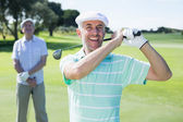 Golfer swinging his club with friend — Stok fotoğraf