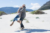Couple playing on the beach in warm clothing — Stock Photo