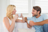 Couple on couch having coffee — Stock Photo