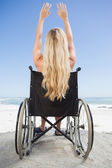 Wheelchair bound blonde with arms up — Stock Photo